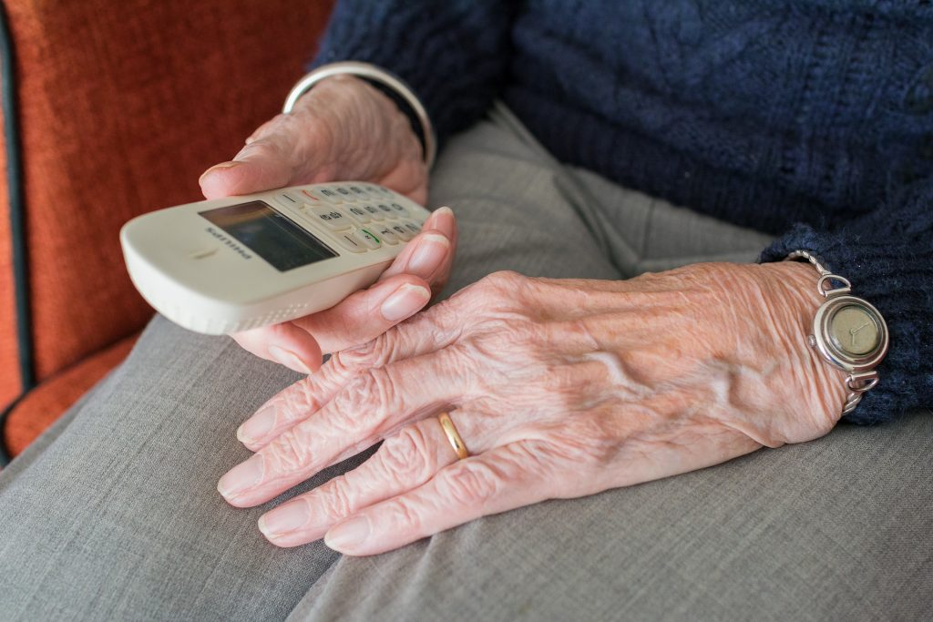 Senior holding a remote