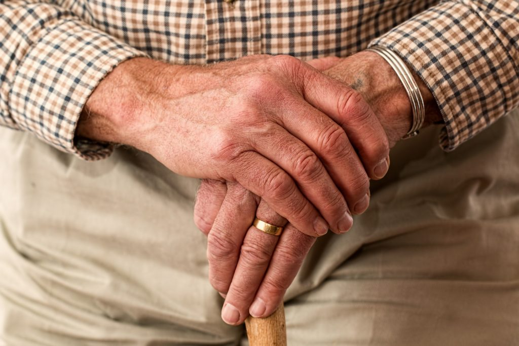 Elderly person's hands on cane