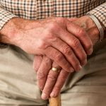Elderly man holding cane