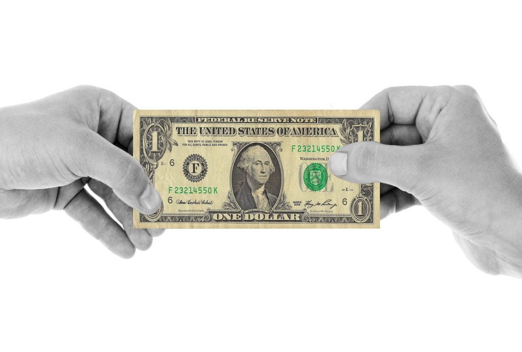Two hands holding a dollar bill